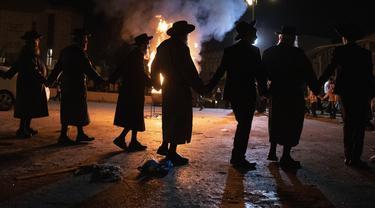 Pria Ultra-Ortodoks Yahudi menari di samping api unggun di Yerusalem, Kamis (29/4/2021). Selama liburan Lag Ba'Omer, menandai berakhirnya wabah yang dikatakan telah membinasakan orang Yahudi selama zaman Romawi. (AP Photo/Sebastian Scheiner)
