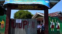 MUrid SD Negeri 62 Kota Bengkulu terpaksa masuk ke sekolah dengan pintu yang hanya dibuka beberapa jengkal saja. (Liputan6.com/Yuliardi Hardjo)