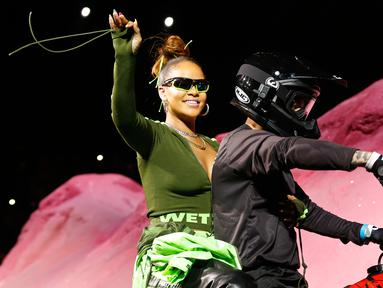 Penyanyi Rihanna menyapa penonton saat berada di motor trail membawakan busana koleksi dari Fenty Puma musim semi 2018 selama New York Fashion Week di New York, AS (10/9). (AP Photo / Bebeto Matthews)