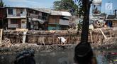 Sejumlah rumah hampir ambruk akibat amblesnya tanah di bantaran Anak Kali Ciliwung di Jalan Lodan Raya, Pademangan, Jakarta, Senin (19/11). Amblesnya bangunan akibat pengerukan untuk normalisasi kali dan pemasangan turap. (Liputan6.com/Faizal Fanani)
