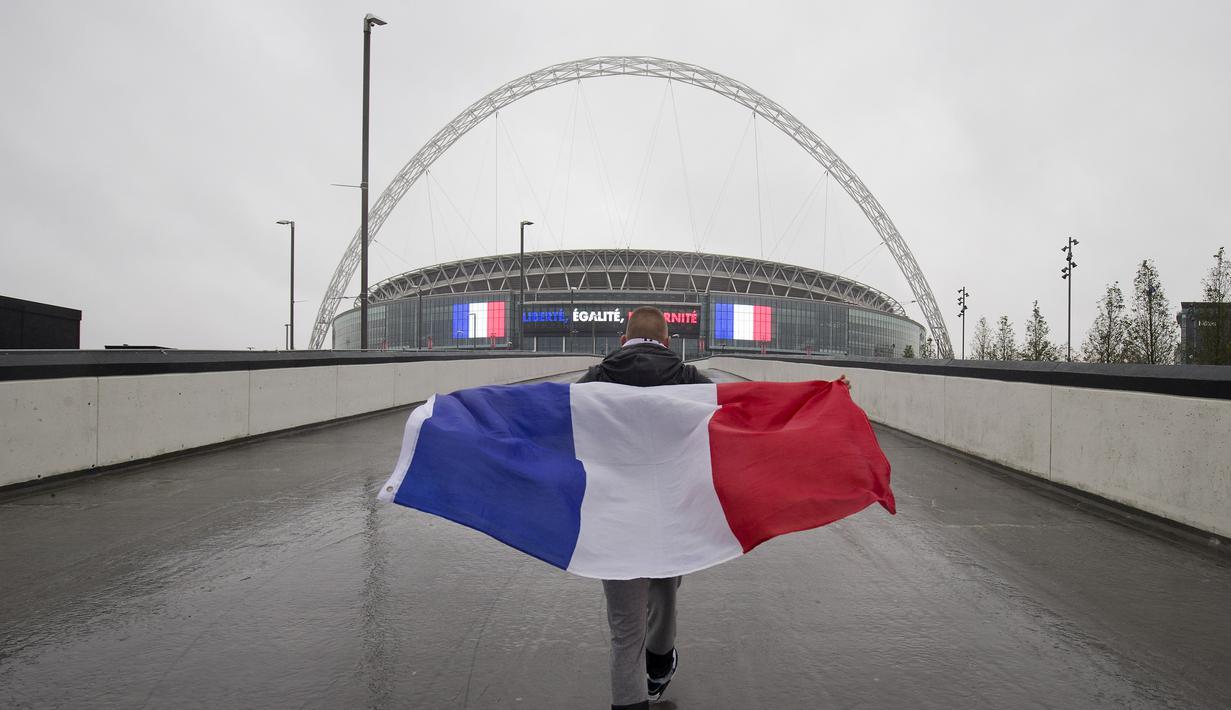 Seorang suporter Prancis membawa bendera Prancis saat menuju Stadion Wembley, London, jelang pertandingan persahabatan antara Inggris melawan Prancis, Selasa (17/11/2015). (AFP Photo/Justin Tallis)