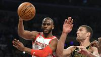 Guard Houston Rockets Chris Paul (kiri) mengumpan bola melewati center Los Angeles Lakers Brook Lopez pada lanjutan NBA 2017-2018 di Staples Center, Selasa (10/4/2018) Rabu (11/4/2018) WIB. (AP Photo/Mark J. Terrill)