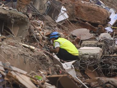 Seorang petugas penyelamat mencari orang-orang di reruntuhan gedung apartemen berlantai lima yang runtuh di Mahad, India (25/8/2020). Tim penyelamat dan anjing pelacak menyisir puing-puing mencari yang selamat setelah gedung apartemen berlantai lima runtuh. (AFP Photo/Punit Paranjpe)