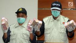 Petugas KPK menunjukkan barang bukti uang hasil OTT di dua wilayah Kota Blitar dan Kabupaten Tulungagung, Jakarta, Jumat (9/6). KPK berhasil mengamankan uang 2,5 Miliar yang diduga suap proyek di dua wilayah kota tersebut. (Merdeka.com/Dwi Narwoko)