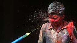 Seorang anak India terkena semprotan air berwarna selama festival Holi di Chennai (2/3). Holi, festival musim semi hindu di India yang diadakan 2 Maret tahun ini pada akhir musim dingin pada bulan purnama pertama kalender lunar. (AFP Photo/Arun Sankar)