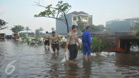 Petugas dibantu warga membetulkan  tanggul yang jebol di kawasan Perumahan Pantai Mutiara, Jakarta, Sabtu (4/6). Akibat tanggul jebol kawasan tersebut tergenang dengan ketinggian 50-60 sentimeter. (Liputan6.com/Gempur M Surya)