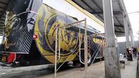 Bus baru Arema saat dicat di dekat Bandara Abdulrachman Saleh, Malang (5/3/2020). (Bola.com/Iwan Setiawan)