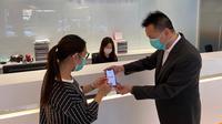 Seorang pegawai sedang membantu nasabah untuk melakukan aktivasi BNI Mobile Banking di BNI Hong Kong pada Selasa (24/3/2020).