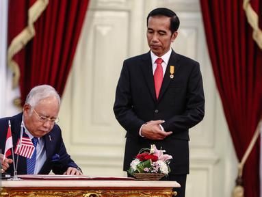 PM Malaysia, HE Dato Sri Muhammad Najib Tun Abdul Razak (kiri) mengisi buku tamu dampingi Presiden Jokowi di Istana Merdeka, Jakarta, Senin (1/8). Pertemuan membahas Konsultasi Bilateral Tahunan RI-Malaysia ke-11. (Liputan6.com/Faizal Fanani)