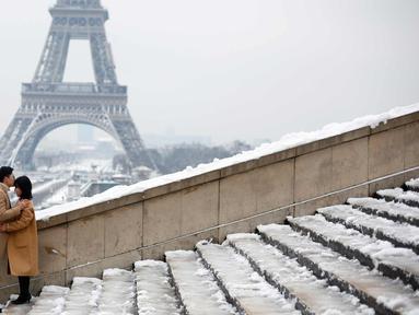 Pasangan berpose di depan Menara Eiffel di Paris, Prancis (7/2). Hujan salju yang sangat lebat membuat transportasi umum di paruh utara Prancis dan di Paris tidak dapat beroperasi. (AP Photo / Thibault Camus)