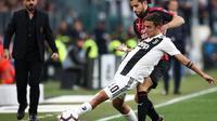 Penyerang Juventus, Paulo Dybala (depan), berjibaku kontra bek AC Milan, Ricardo Rodriguez, Sabtu (6/4/2019), di Juventus Stadium.  (AFP / Isabella Bonotto)