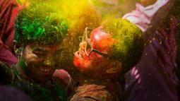 Orang-orang menari dan melempar bubuk berwarna saat Festival Holi di Gauhati, India, Selasa (10/3/2020). Festival Holi menandai datangnya musim semi di India. (AP Photo/Anupam Nath)