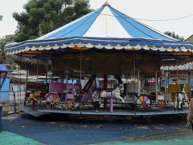 Seorang wanita berdiri dekat wahana permainan anak yang berhenti beroperasi di pinggir Kanal Banjir Timur, Jakarta, Sabtu (2/5/2020). Wahana permainan anak tersebut sudah satu bulan lebih berhenti beroperasi karena pemberlakuan PPSBB untuk memutus penyebaran pandemi COVID-19. (merdeka.com/Imam Buhor