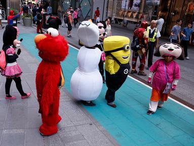 Sejumlah karakter kartun berada di jalanan untuk menghibur pengunjung di Times Square, New York, Selasa (21/6). Kehadiran karakter-karakter kartun tersebut mengundang warga untuk foto bersama. (REUTERS/Lucas Jackson)