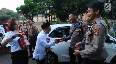 Relawan GOJO (Golkar Jokowi) memberikan makanan berbuka kepada para aparat yang melakukan penjagaan gedung KPU, Menteng, Jakarta Pusat, Kamis (23/5/). Makanan berbuka puasa ini diberikan sebagai bantuan kepada para aparat yang telah menjaga keamanan gedung KPU. (Liputan6.com/Angga Yuniar)