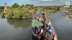 Perahu wisata melintasi kerumunan wisatawan yang berjalan di atas Jembatan Cinta di Wisata Mangrove, Tarumajaya, Bekasi, Minggu (30/12). Wisata tersebut menyajikan hutan mangrove dan makanan khas. (merdeka.com/Arie Basuki)