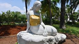 Patung putri duyung yang bagian dadanya ditutup kain berwarna emas di kawasan Putri Duyung Resort Ancol, Jakarta, Selasa (26/3). Patung putri duyung putih yang tampak seperti mengenakan kemben itu ramai diperbincangkan di media sosial. (Photo by ADEK BERRY / AFP)
