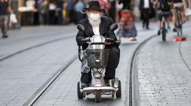 Seorang pria Yahudi Ultra-Ortodoks tua, yang mengenakan masker karena pandemi virus corona COVID-19, mengendarai skuter mobilitas roda tiga di sepanjang jalan di Yerusalem (26/10/2020). (AFP/Emmanuel Dunand)