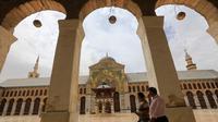 Dua pria Suriah berjalan melintasi masjid bersejarah Umayyad di kota lama Damaskus, Selasa (22/5). Masjid yang juga dikenal sebagai Masjid Agung Damaskus itu merupakan salah satu masjid terbesar dan tertua di dunia. (AFP PHOTO/LOUAI BESHARA)