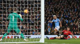 Striker Manchester City, Sergio Aguero melepaskan tendangan ke arah kiper MU, David De Gea saat bertanding pada lanjutan Liga Inggrid di stadion Etihad, Manchester (11/11). Sebelumnya, rambut Aguero berwarna hitam biasa. (AFP Photo/Lindsey Parnaby)