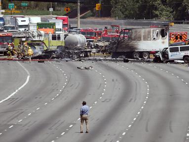 Penyidik memeriksa bangkai truk yang telah hangus usai terjadi tabrakan antara dua truk besar di utara pusat kota Los Angeles (25/4). Kecelakaan ini menewaskan satu orang dan melukai sejumlah orang lainnya. (AP Photo/Reed Saxon)