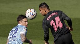 Gelandang Real Madrid, Casemiro (kanan) menyundul bola dari ancaman striker Celta Vigo, Santi Mina dalam laga lanjutan Liga Spanyol 2020/2021 pekan ke-28 di Balaidos Stadium, Sabtu (20/3/2021). Real Madrid menang 3-1 atas Celta Vigo. (AP/Lalo R. Villar)