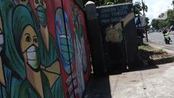 Pengedara motor melintas di depan mural tentang pandemi virus COVID-19 di Jalan Raya Jakarta-Bogor, Depok, Jawa Barat, Selasa (7/4/2020). Mural tersebut sebagai bentuk dukungan kepada tenaga medis yang menjadi garda terdepan menghadapi COVID-19 di Indonesia. (Liputan6.com/Helmi Fithriansyah)