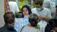 Pedagang melayani pembeli di salah satu toko penjualan masker di Pasar Pramuka, Jakarta Timur, Rabu (4/3/2020). Polda Metro Jaya menggelar sidak di Pasar Pramuka untuk menyikapi lonjakan harga dan kelangkaan masker di pasaran terkait virus corona atau COVID-19. (merdeka.com/Imam Buhori)