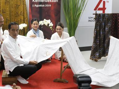 Presiden Joko Widodo didampingi Ibu Negara Iriana Jokowi saat membatik di acara batik kemerdekaan di Stasiun MRT Bundaran HI, Kamis (1/8/2019). Dalam kesempatan tersebut Jokowi berharap batik bisa dikembangkan sebagai sebuah brand. (Liputan6 com/Angga Yuniar)