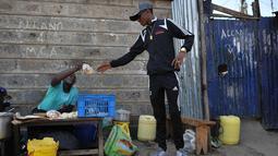 Artis hip hop Kenya Henry Ohanga alias Octopizzo yang berasal dari Kibera kumuh terbesar di Kenya di Nairobi, membeli makanan ringan dari penjual pinggir jalan saat berkunjung ke Kibera pada 16 Januari 2018. (AFP Photo/Tony Karumba)
