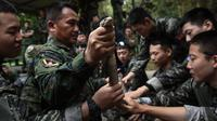 Marinir Thailand menunjukkan ular kobra yang digunakan saat latihan gabungan Cobra Gold antara militer AS dan Thailand di Chonburi, Thailand (19/2). Dalam latihan ini mereka berlatih bertahan hidup saat berada di hutan. (AFP Photo/Lilian Suwanrumpha)