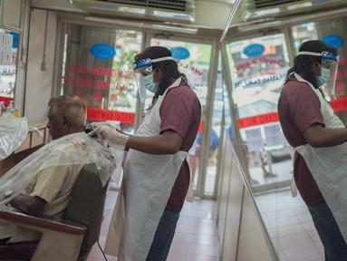 Seorang barber memangkas rambut pelanggan di sebuah tempat pangkas rambut di Kuala Lumpur, Malaysia, pada 10 Juni 2020. (Xinhua/Zhu Wei)