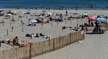 """Orang-orang menikmati sore dengan area terpisah untuk mematuhi jaga jarak di pantai """"Plage du Couchant"""" di La Grande-Motte, Prancis Selatan, Selasa (26/5/2020). Otoritas setempat membuat kotak-kotak yang dapat ditempati para pengunjung tetap bisa menjaga jarak fisik di pantai. (Pascal GUYOT/AFP)"""