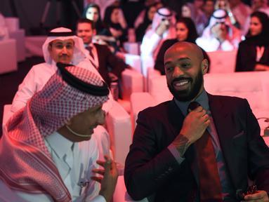 Mantan pemain Arsenal, Thierry Henry (tengah) merapihkan dasi saat menghadiri konferensi Quality of Life Program 2020 di ibukota Saudi Riyadh (3/5). Program ini adalah salah satu program realisasi visi Arab Saudi 2030. (AFP Photo/Fayez Nureldine)