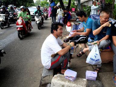 Para pencari suaka bercengkerama di trotoar depan Rumah Detensi Imigrasi Kalideres, Jakarta, Jumat (19/1). Selama 17 minggu, sebanyak 57 WNA tinggal di trotoar karena ruangan Rumah Detensi Imigrasi tersebut penuh. (Liputan6.com/JohanTallo)