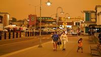 Sejumlah orang berjalan saat kabut asap menyelimuti langit di Fisherman's Wharf, San Francisco, Amerika Serikat, Rabu (9/9/2020). Kebakaran hutan di seluruh Barat mengakibatkan langit San Francisco hingga Seattle berwarna oranye yang menakutkan. (AP Photo/Eric Risberg)