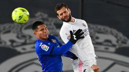 Bek Real Madrid, Nacho Fernandez (kanan) berduel udara dengan striker Getafe, Cucho Hernandez dalam laga lanjutan Liga Spanyol 2020/21 pekan ke-22 di Alfredo di Stefano Stadium, Selasa (9/2/2021). Real Madrid menang 2-0 atas Getafe. (AFP/Gabriel Bouys)