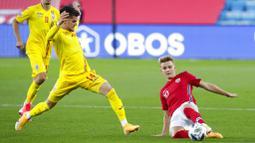 Pemain Norwegia, Martin Odegaard, berebut bola dengan pemain Rumania, Ianis Hagi, pada laga UEFA Nations League di Stadion Ullevaal, Minggu (11/10/2020). Norwegia menang dengan skor 4-0. (Vidar Ruud /NTB scanpix via AP)