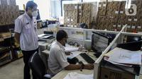 Pegawai Badan Kepegawaian Daerah DKI Jakarta menyelesaikan pekerjaannya di Kantor Balai Kota DKI Jakarta, Kamis (11/2/2021). Kementerian PANRB secara resmi melarang seluruh ASN bepergian ke luar kota saat libur Imlek guna mencegah penyebaran dan penularan COVID-19. (Liputan6.com/Johan Tallo)