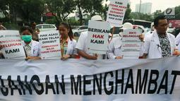 Sejumlah massa yang menamakan diri dari Pergerakan Dokter Muda Indonesia membentangkan spanduk saat melakukan aksi di depan Istana Negara, Jakarta, Kamis (19/7). (Liputan6.com/Johan Tallo)