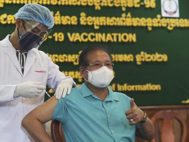 Direktur Kementerian Informasi Kamboja Jenderal Ly Vannhong (kanan) menerima suntikan vaksin COVID-19 Sinovac di Kementerian Informasi selama kampanye inokulasi melawan virus corona di Phnom Penh, Kamboja, Kamis (1/4/2021).  (AP Photo/Heng Sinith)