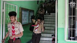 Sejumlah siswa berlarian menyelamatkan diri saat simulasi bencana di SMA Negeri 78 Jakarta, Rabu (23/1). Kegiatan itu untuk pengenalan kepada siswa-siswi dengan program siaga bencana berupa simulasi evakuasi gempa dan tsunami. (Liputan6.com/Faizal Fanani)
