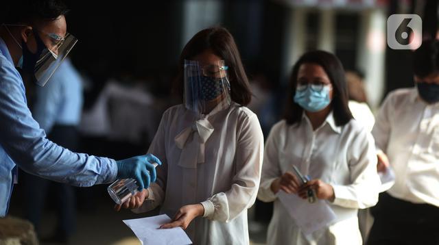 Petugas memberikan cairan hand sanitizer kepada peserta yang bersiap mengikuti Seleksi Kompetensi Bidang (SKB) berbasis Computer Assisted Test (CAT) untuk Calon Pegawai Negeri Sipil (CPNS) Kemenkumham di Gedung Kepegawaian Negara, Jakarta, Rabu (2/9/2020). (merdeka.com/Imam Buhori)