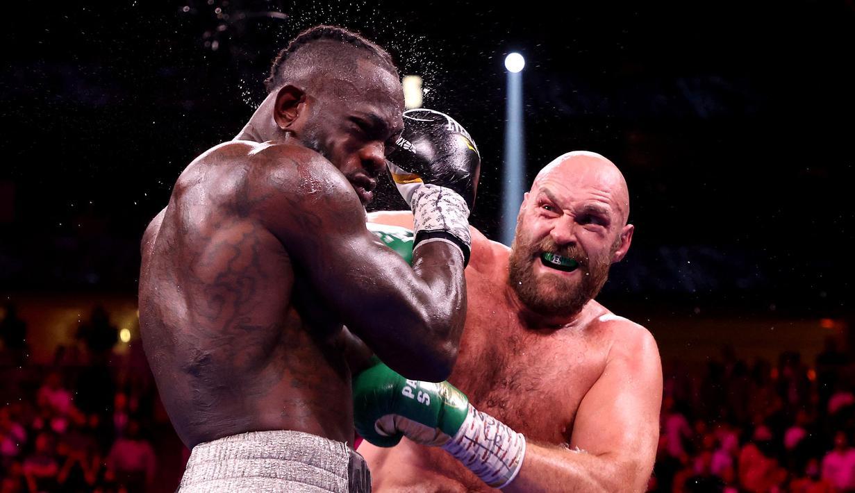 Tyson Fury berhasil mempertahankan gelar juara kelas verat versi WBC. Menghadapi Deontay Wilder dalam duel trilogi di MGM Arena, Minggu pagi WIB (10/10/2021), Fury sukses menang KO. (AFP via Getty Images/Al Bello)