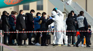 Penumpang menjalani pemeriksaan saat turun dari pesawat yang membawa warga Prancis dari Wuhan di Pangkalan Udara Istres-Le Tube, Istres, Prancis, Minggu (2/2/2020). Sebanyak 65 warga Perancis menjalani karantina setelah dipulangkan dari Wuhan menyusul wabah virus corona. (Photo by Handout/ECPAD/AFP)