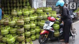Warga mengangkut tabung gas LPG 3 kilogram (kg) dengan sepeda motor di Jakarta, Rabu (16/12/2020). PT Pertamina (Persero) memperkirakan kebutuhan gas elpiji 3 kg naik menjadi 7,50 juta metrik ton pada 2021. (Liputan6.com/Angga Yuniar)