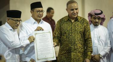 Menag Lukman Hakim Saifuddin menunjukan surat yang usai ditanda tangani saat meresmikan pemajangan potongan Kiswah (kain penutup Kakbah) hadiah dari Raja Salman bin Abdulaziz Al Saud di Masjid Istiqlal, Jakarta, Jumat (10/3). (Liputan6.com/Faizal Fanani)