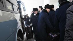 Rombongan grup orkestra Korut masuk ke dalam bus saat tiba di kantor transit Korea di DMZ yang membagi kedua Korea di Paju (5/2). 140 anggota orkestra Korut akan tampil pada perhelatan Olimpiade Musim Dingin 2018. (AFP Photo/Pool/Jung Yeon-Je)