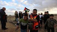Petugas medis Palestina membantu seorang anak laki-laki yang terluka dalam bentrokan dengan tentara Israel di dekat wilayah perbatasan dengan Israel, Kota Gaza timur, pada 6 Desember 2019. (Xinhua/Mohammed Dahman)