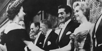 Ini adalah Marilyn Monroe di tahun 1956 saat ia bertemu dengan Ratu Elizabeth. Marilyn Monroe mengenakan strapless dress dengan sarung tangan panjang. Foto: Website.